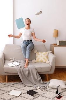 女の子は家のソファに座って本と笑顔を投げる