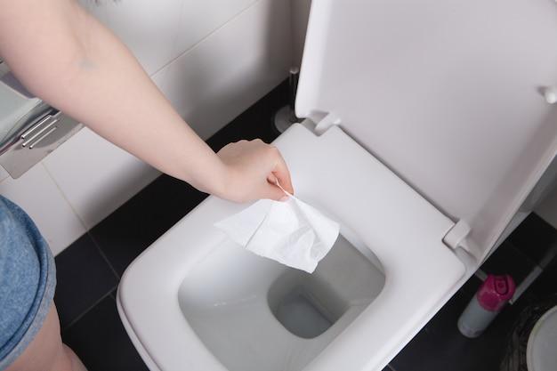 Девушка бросает бумагу в унитаз
