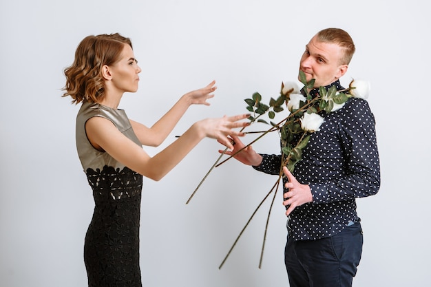 The girl throws the roses given to her at her boyfriend.