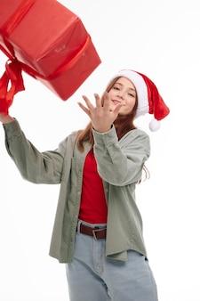 Девушка подбрасывает красную коробку праздничного подарка веселого нового года. фото высокого качества
