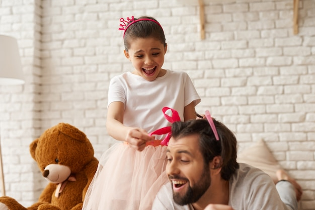 Girl tie dads hair in pigtail with gift ribbon.