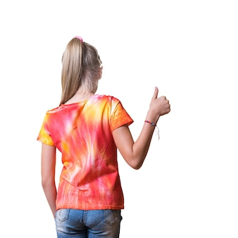 A girl in a tie dye t-shirt shows a thumbs up isolated. white clothes painted by hand.