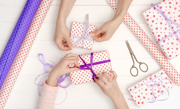 Girl tied ribbon on the gift