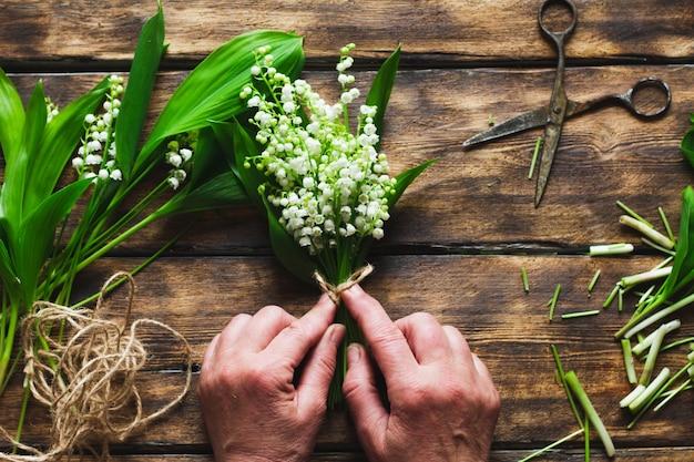 소녀는 계곡의 백합 꽃다발을 묶어