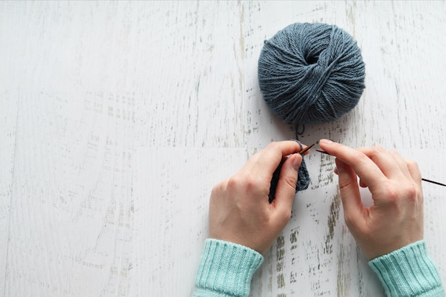 The girl ties gray yarn, light surface