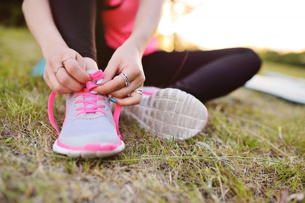 女の子はスニーカーの靴ひもを結ぶ