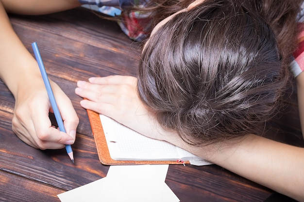 Girl tired student falls asleep, study session