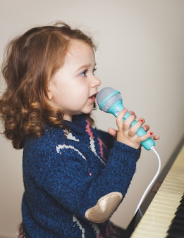 Girl toddler, piano and toy microphone.