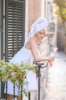 Девушка приняла душ и стоит на балконе в южном городе и пьет белое вино из бокала.