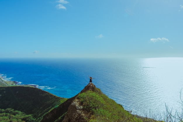 Girl on top of the mountain overlooking the ocean