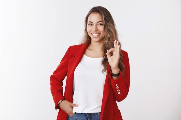 Девушка уверенно заверила себя руками, показывая ладно ладно жестом улыбаясь счастливому самоуверенному держанию руки в кармане. успешная деловая женщина довольна всем в порядке
