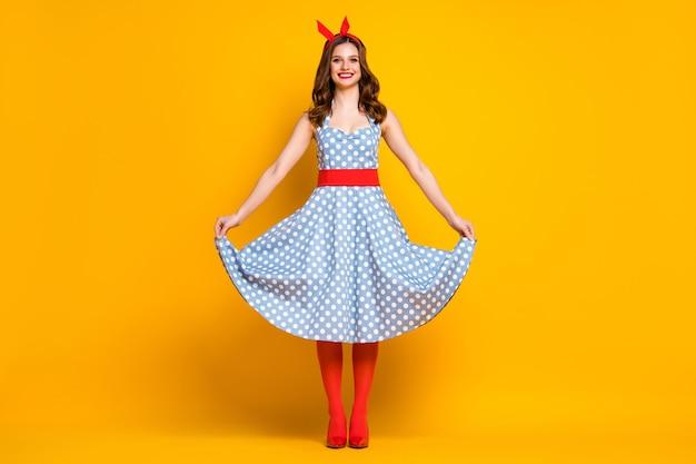 女の子は黄色の背景に彼女の水玉模様のドレススタンドに触れます