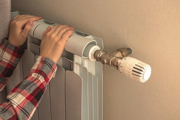 Девушка трогает радиатор отопления дома, концепция зимнего холода