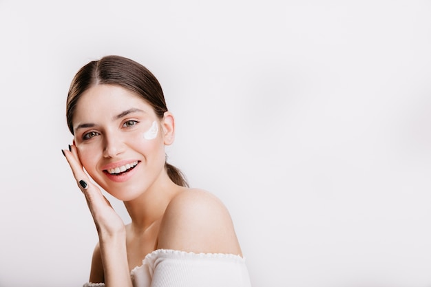 Girl touches moisturized skin and smiles. portrait of model with cream on face on isolated wall.