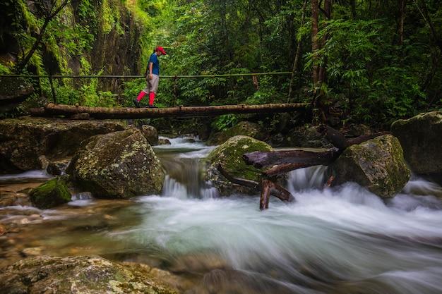 The girl touring on pi-tu-gro waterfall, beautiful waterfall in tak province, thailand.