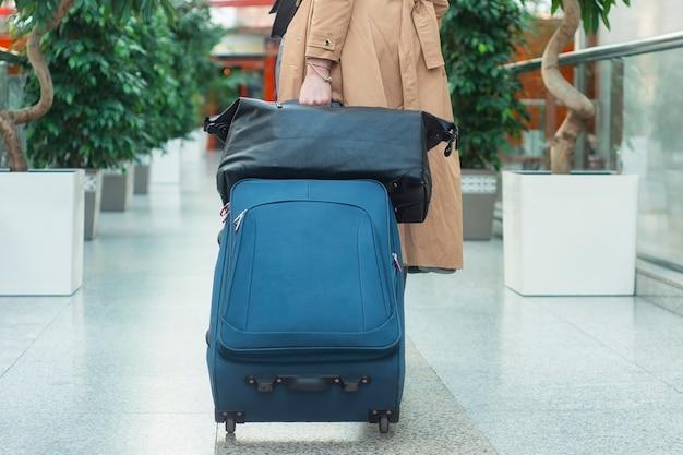 Девушка-турист в аэропорту несет чемодан на колесах с сумкой. концепция на тему туризма.