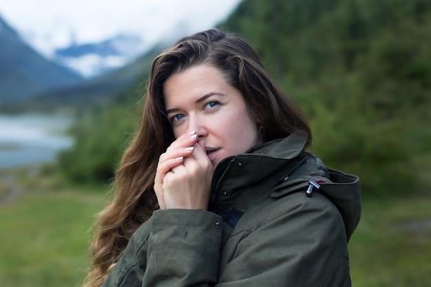 少女観光客は山で寒い朝に彼らを暖める彼女の手を吹く
