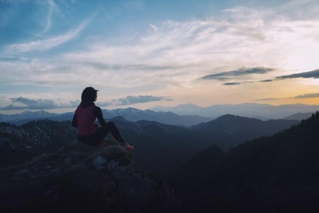 夕暮れ時の山の風景を楽しむ女の子観光客