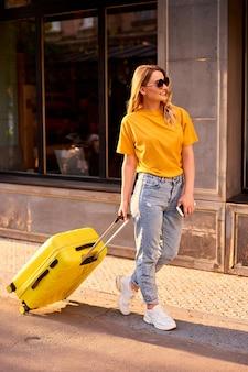 Девушка-турист держит в руках мобильный телефон, гуляет по городу с желтым чемоданом и смотрит правильно