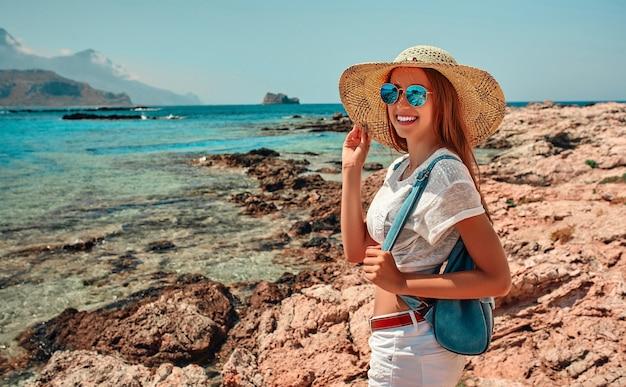 Девушка-турист в соломенной шляпе и шортах с рюкзаком наслаждается морским пейзажем, стоя на берегу и улыбаясь в камеру.