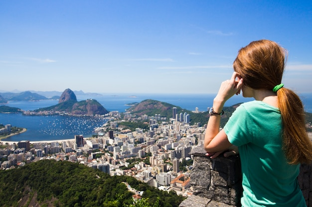 Девушка-турист смотрит на пейзаж рио и пао-ду-асукар
