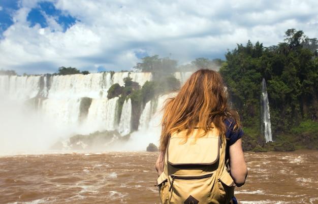 女の子の観光客は、ブラジルとアルゼンチンの国境にある世界的に有名なイグアスの滝の景色を眺めます