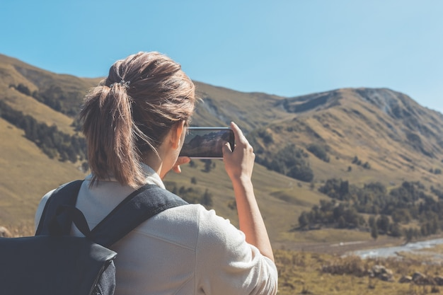 Girl tourist looks at the mountains and makes a photo on a smartphone on a sunny autumn day