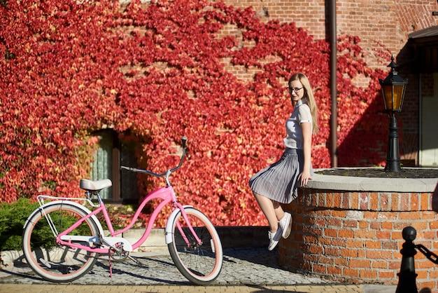 明るく暖かい晴れた秋の日にピンクの女性自転車で低いレンガの壁に座っている女の子の観光