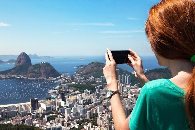 Туристка фотографирует пейзаж рио и пао де асукар со смартфоном, бразилия