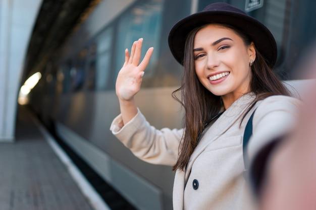 Туристическая девушка делает селфи на вокзале