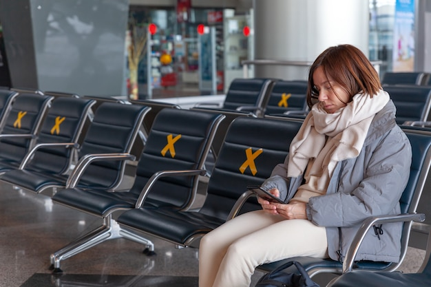 Girl tourist with backpack waiting for flight in airport horizontal