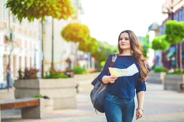 Girl tourist with map in hand on a city street travel guide, tourism in europe