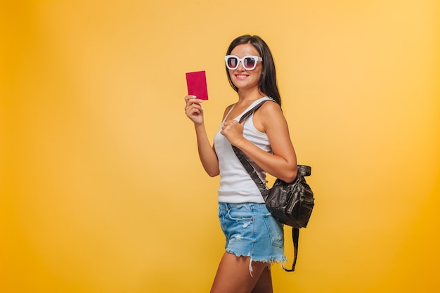 Girl tourist on a yellow background with a backpack and a passport