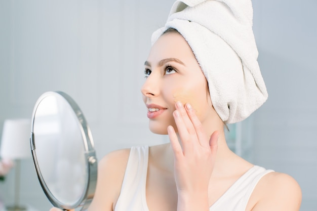 The girl in a towel after a shower, applying tonal cream base on face looking in a mirror.
