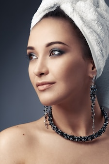 Girl in towel with earrings and necklace