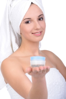 The girl in towels holds on hand a cream.