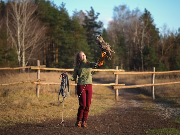 Girl trainer holds an owl on her hand.