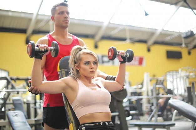 개인 트레이너와 체육관에서 훈련하는 여자