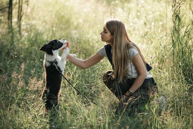 黒と白のボーダーコリー犬の子犬を訓練する女の子