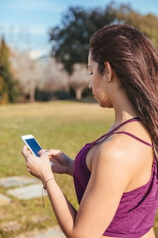 Girl training outdoors looking at her phone