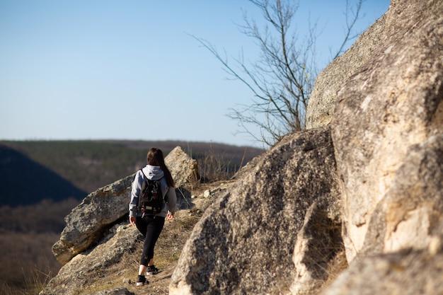 Девушка-путешественница идет в поход с рюкзаком в скалистых горах