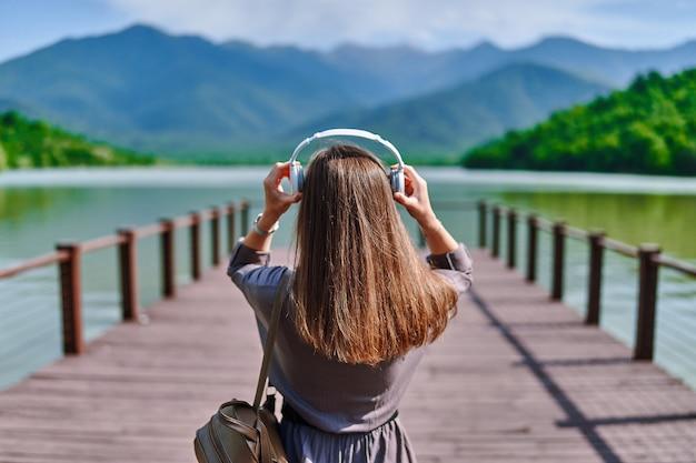 湖と山々の景色を望む桟橋に一人で立って、穏やかで静かで平和な雰囲気を楽しんでいるワイヤレスヘッドフォンで穏やかな音楽を聴いている女の子の旅行者