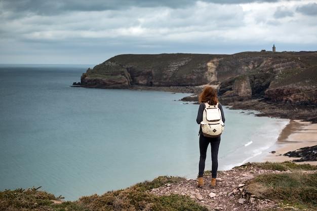 背景のカップフレエルの女の子の旅行者。フランス北部の典型的なブルターニュ海岸