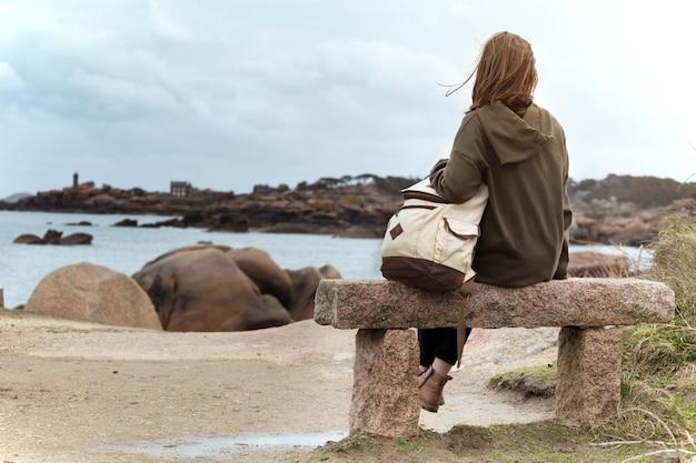 女の子の旅行者は、ブルターニュのトレガステルの海と海岸近くのベンチに座っています。フランス