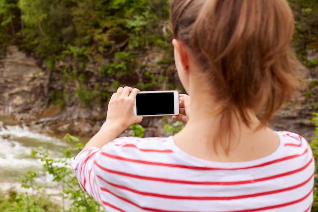 Girl traveler takes lush mountain river in ravine on smartphone, selective focus, enjoing natures landscapes, female wearing stripped shirt, with ponytail. people and traveling concept.