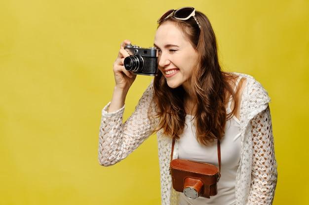 Девушка путешественник фотографирует с камерой винтаж.