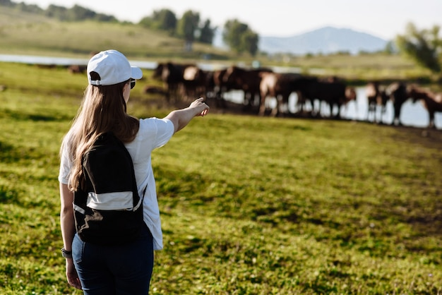 バックパックを背負った少女旅行者が農場の馬に立ち向かう