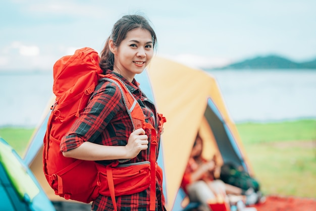 Girl traveler with backpack at campsite on her vacations trip