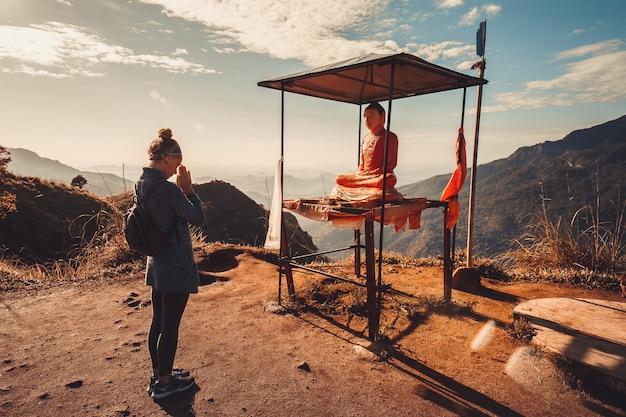 여자 여행자는 스리랑카 산에서 부처를 숭배