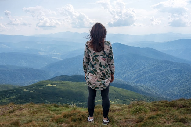 Girl traveling in mountains alone, calm scene. walking outdoors, woman hiker on mountain top. back view over landscape. wanderlust theme. carpathian mountains, view from the mountain